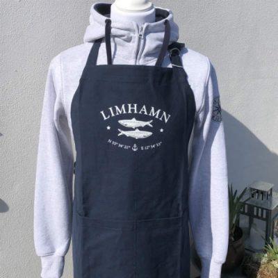 Marinblått förkläde med Limhamn, longitud och latitud och sillar från Kokkolit på Limhamn